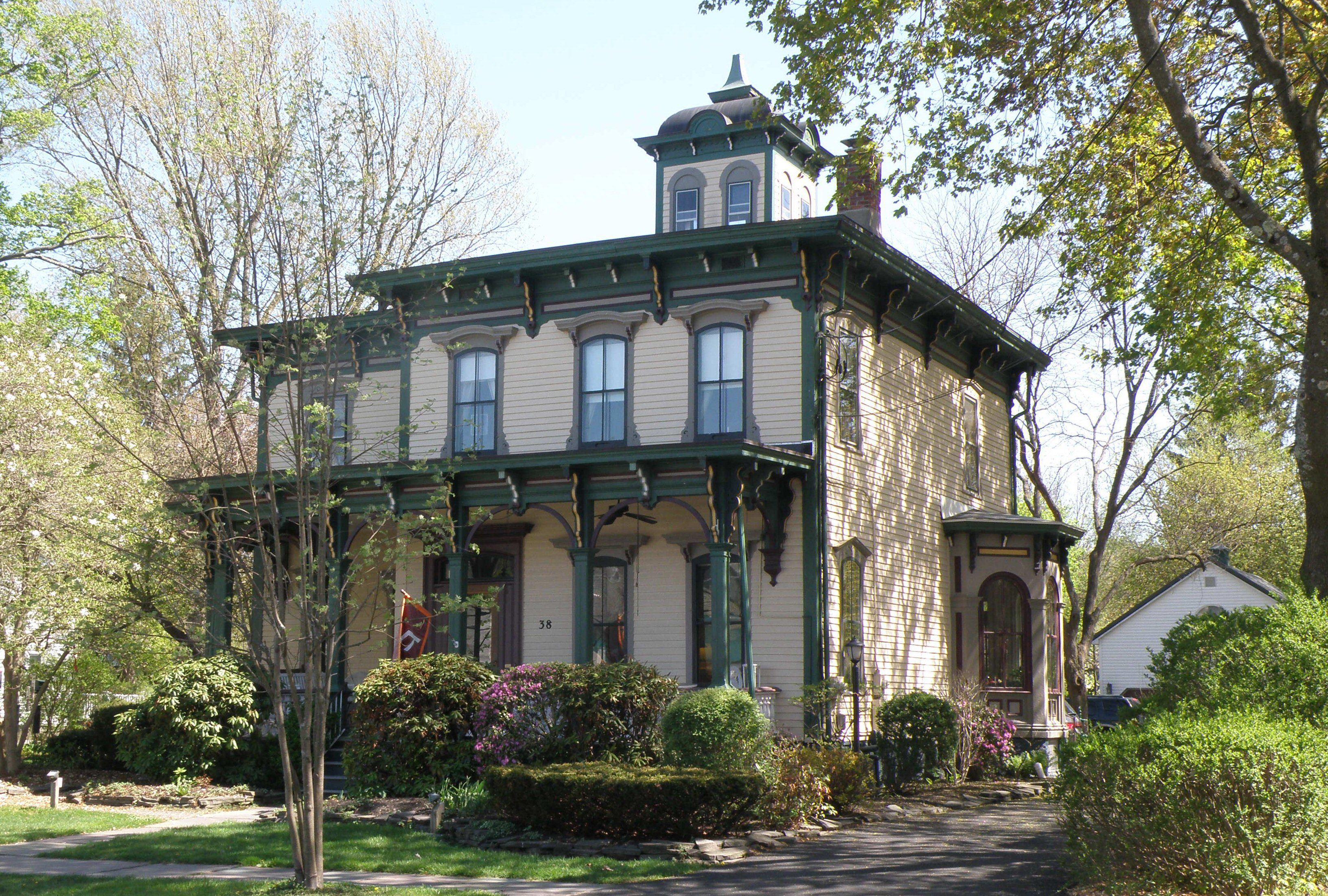 Italianate style house, 2 stories, yellowish siding with green trim and maroon highlights, a square cupola on a flat roof, brackets within the roof overhands and front porch