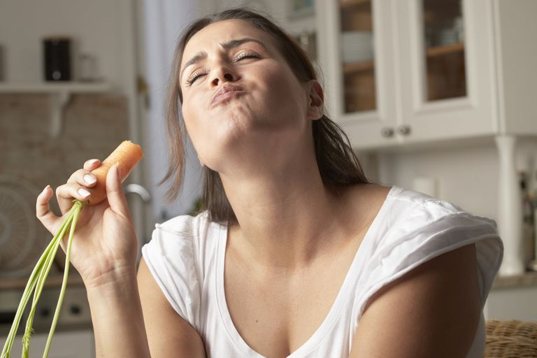 Woman eating a carrot