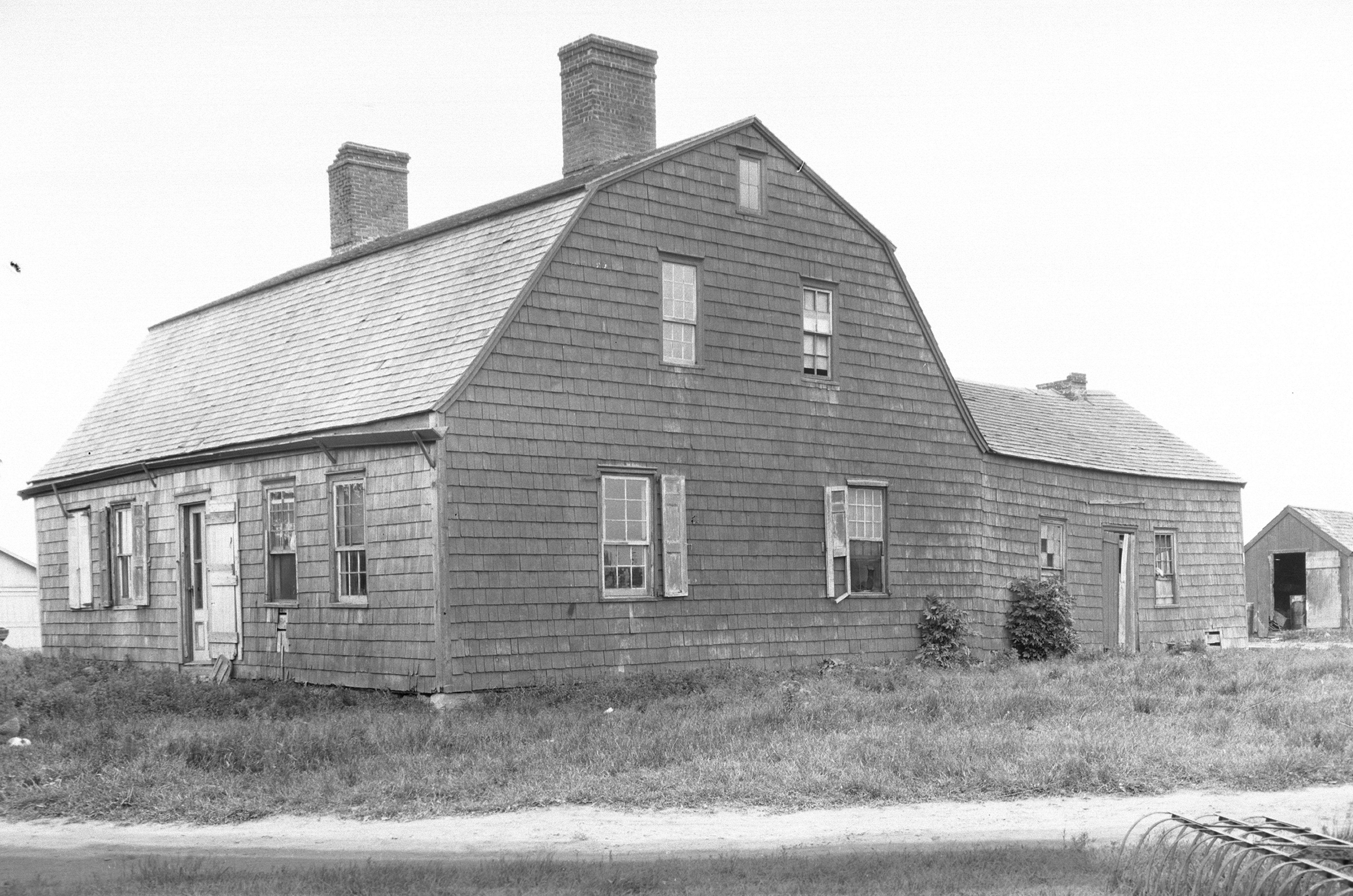 photo historique en noir et blanc de grande maison, vue latérale, deuxième et troisième étages dans le toit en croupe, deux grandes cheminées, outre l'arrière et une grange