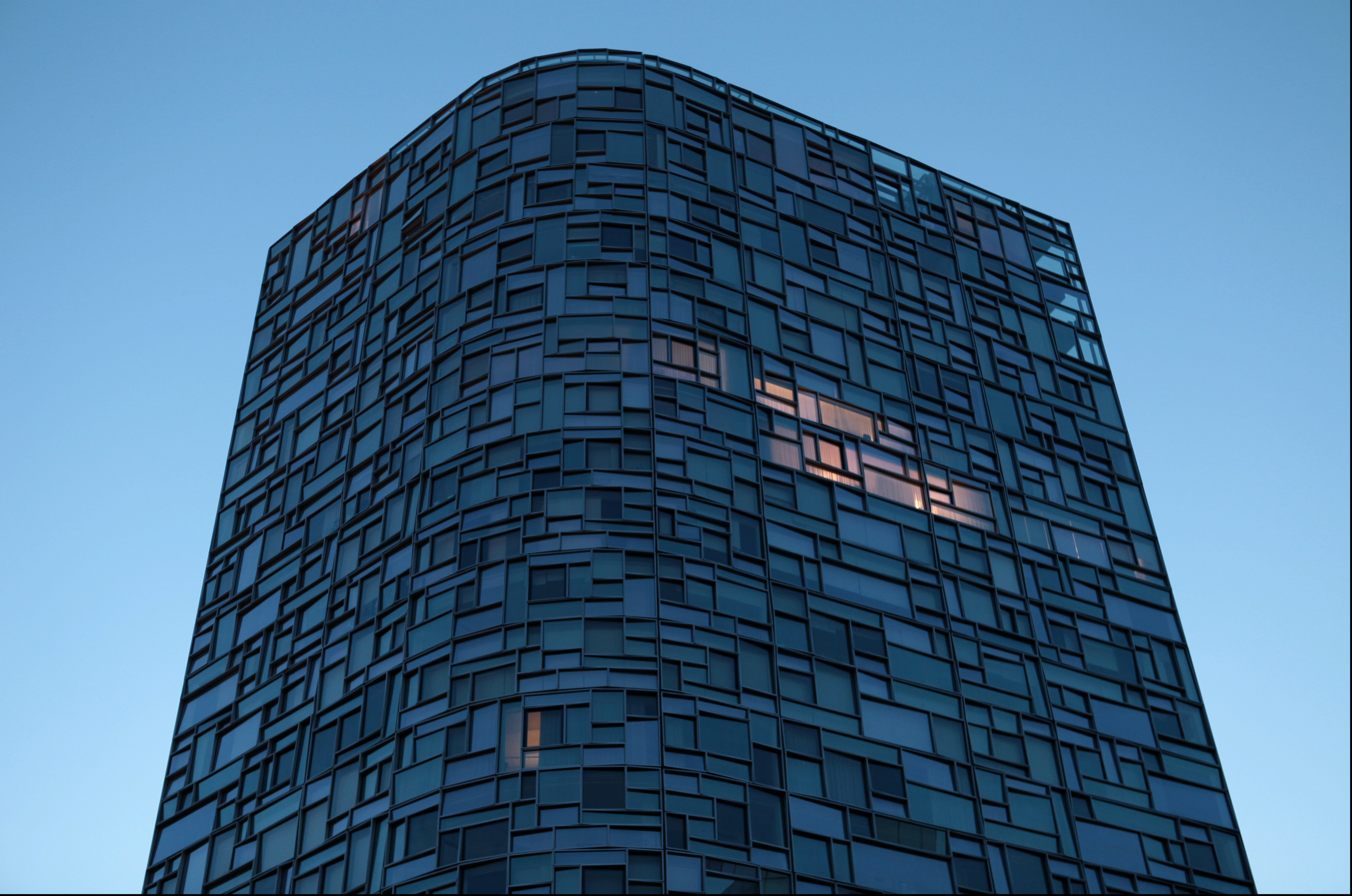 Top view of Nouvel's residential tower, with lights on in a few units with asymmetrical windows