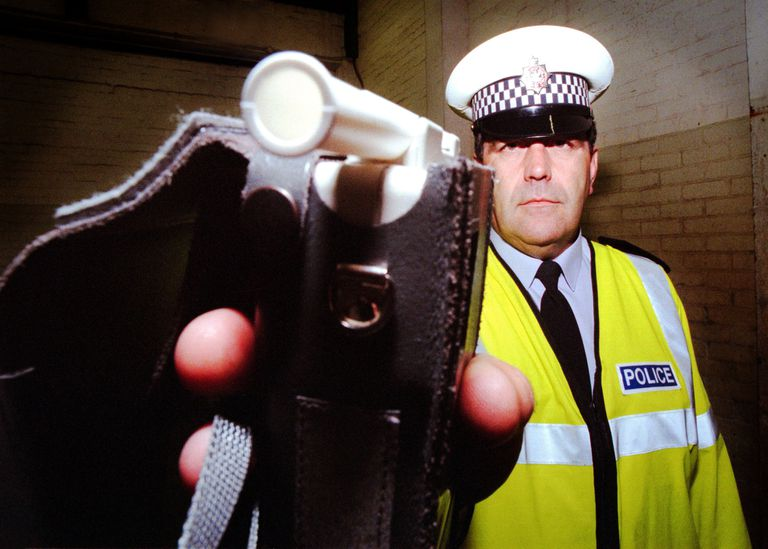 Policeman holdng out a breathalyzer for you to blow in.
