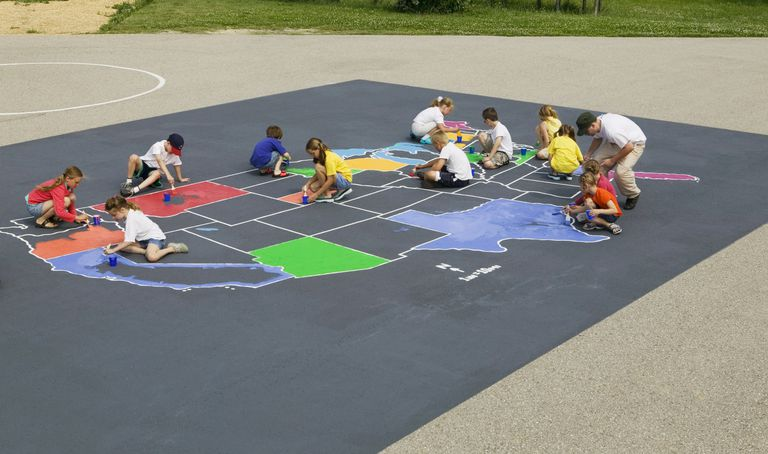 kids drawing U.S. in chalk on the ground