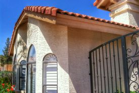 close view of stucco home, clay tile roofing, arched windows, and iron gate