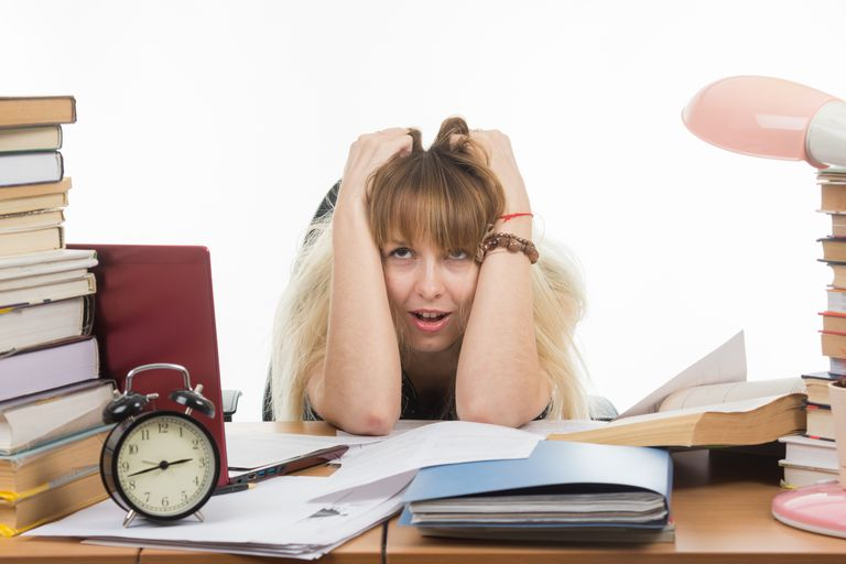 Girl with crowded desk of papers and alarm clock