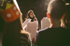 Drama teacher in front of students holding scripts