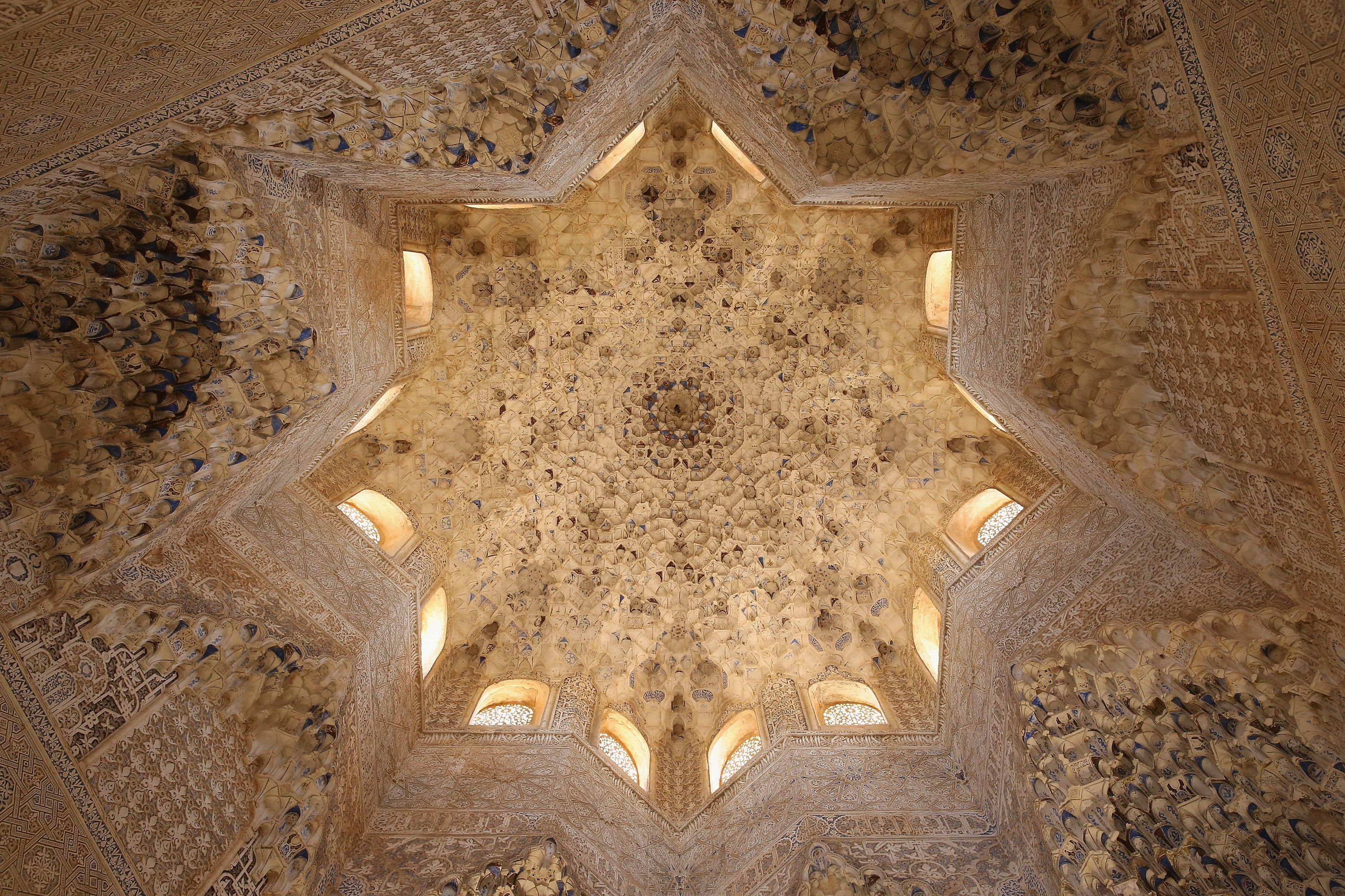 looking up at the ceiling of an ornately carved room, an 8-pointed dome with 16 windows in the sides