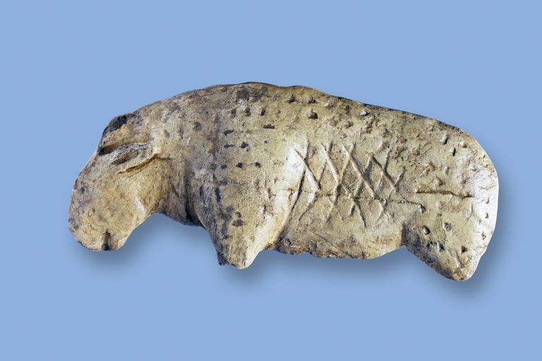 Lion Figurine from Vogelherd Cave against blue background.