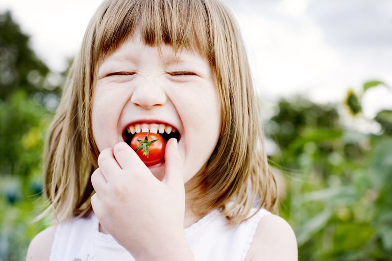 A smiling child bites into a cherry tomato