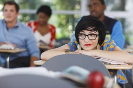 Questioning young woman with glasses at school desk