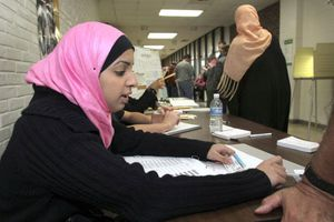 An Arab American election volunteer checks in a voter at the Salina School polling station in Dearborn, Michigan, in the Nov. 2004 Bush-Kerry election. Kerry won Michigan, where almost 500,000 Arab Americans live, but lost the election.