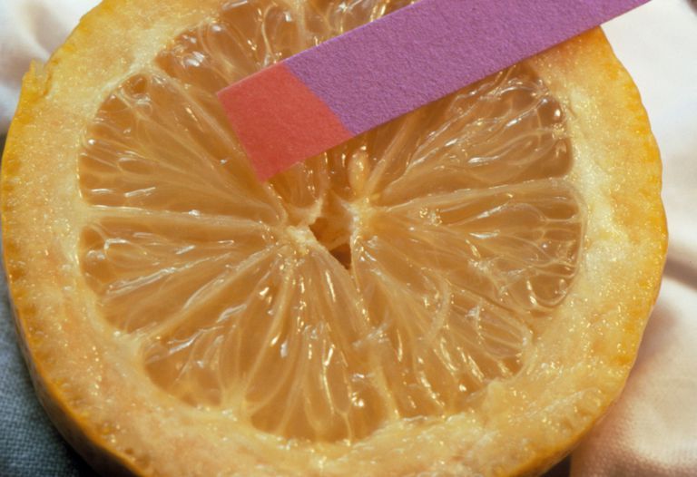 pH strip next to sliced orange