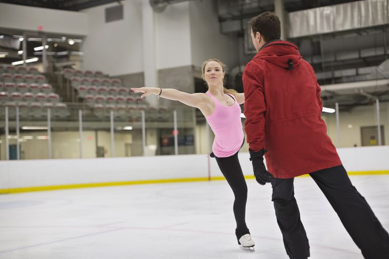 Female figure skater with coach practicing routine in skating rink