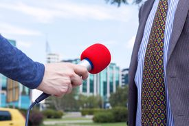 Cropped Hand Of Journalist Holding Microphone By Businessman