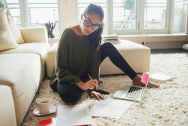 A young woman works on some documents in her living room