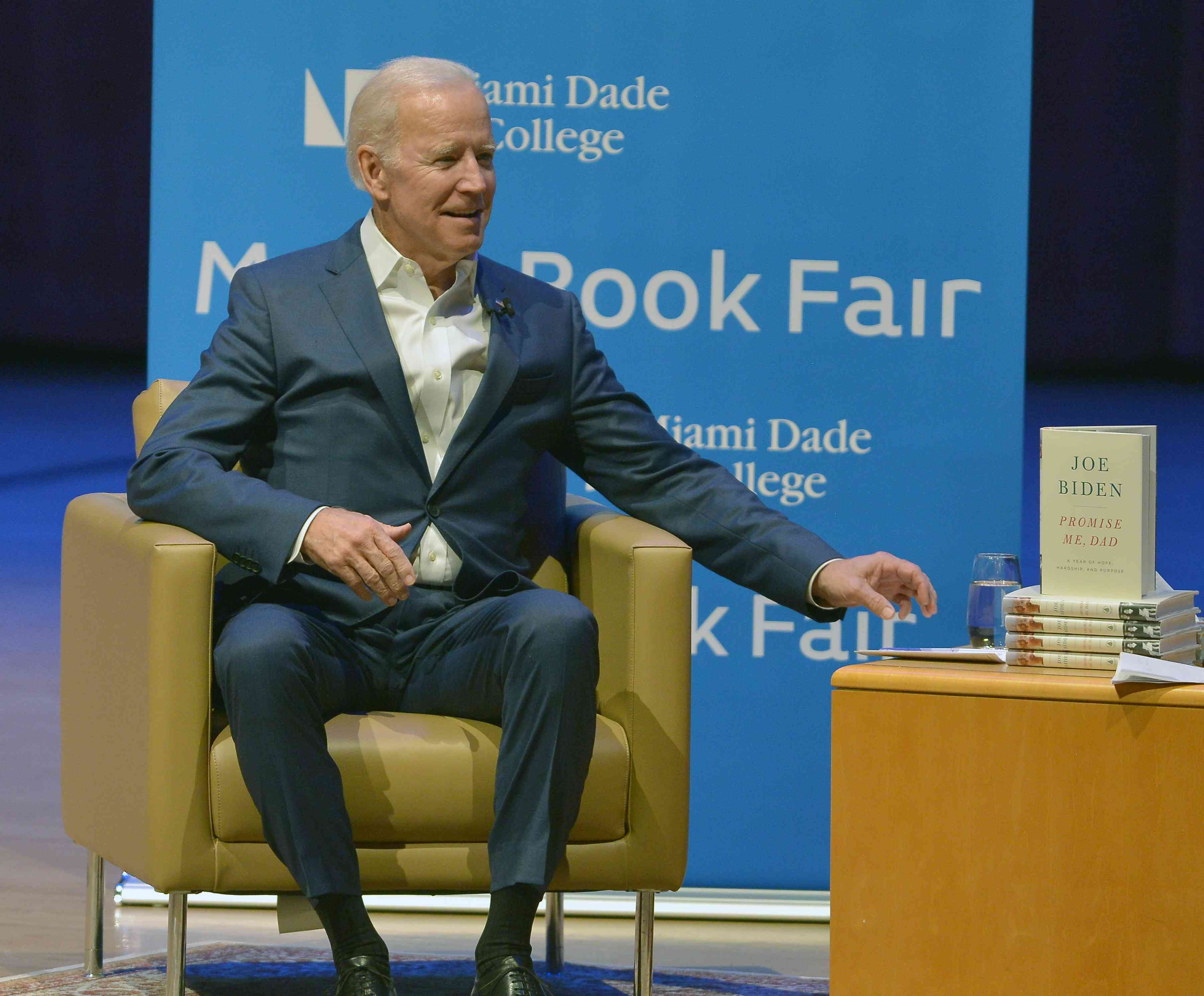 Joe Biden sitting in a chair in front of a blue background, with a stack of books next to him