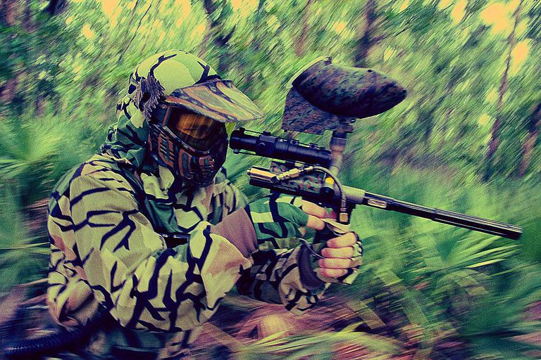 Man in fatigues playing paintball, aiming at target in woods