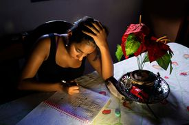 Woman writing in a notebook at night