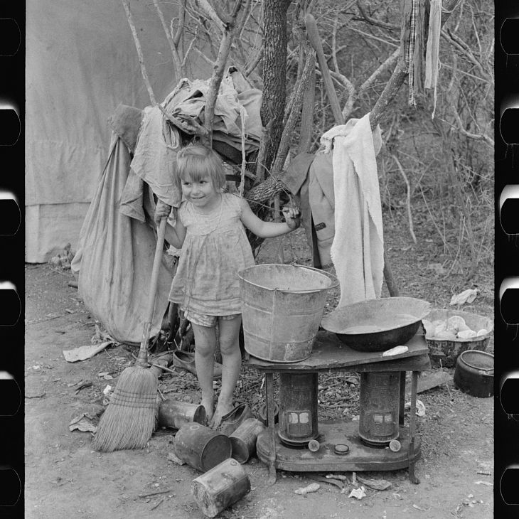 A young girl standing next to an outdoor stove and washstand during the Great Depression.