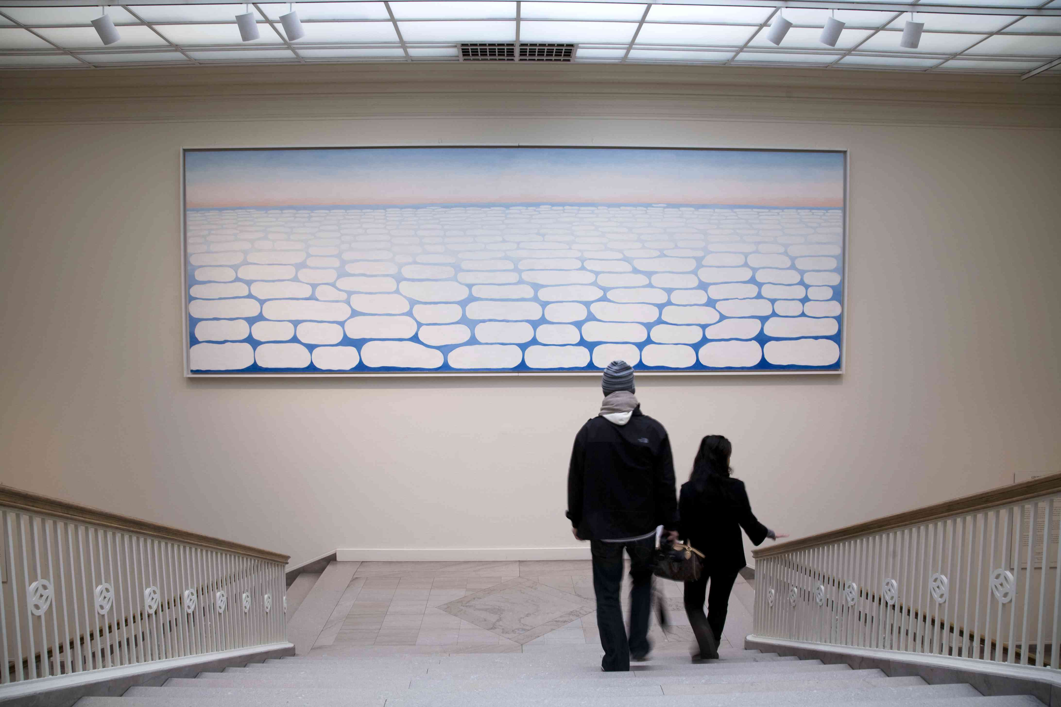 Two people descend the stairs in front of Georgia O'Keeffe's painting of clouds on the horizon