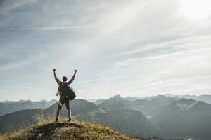 Austria, Tyrol, Tannheimer Tal, young man cheering on mountain top