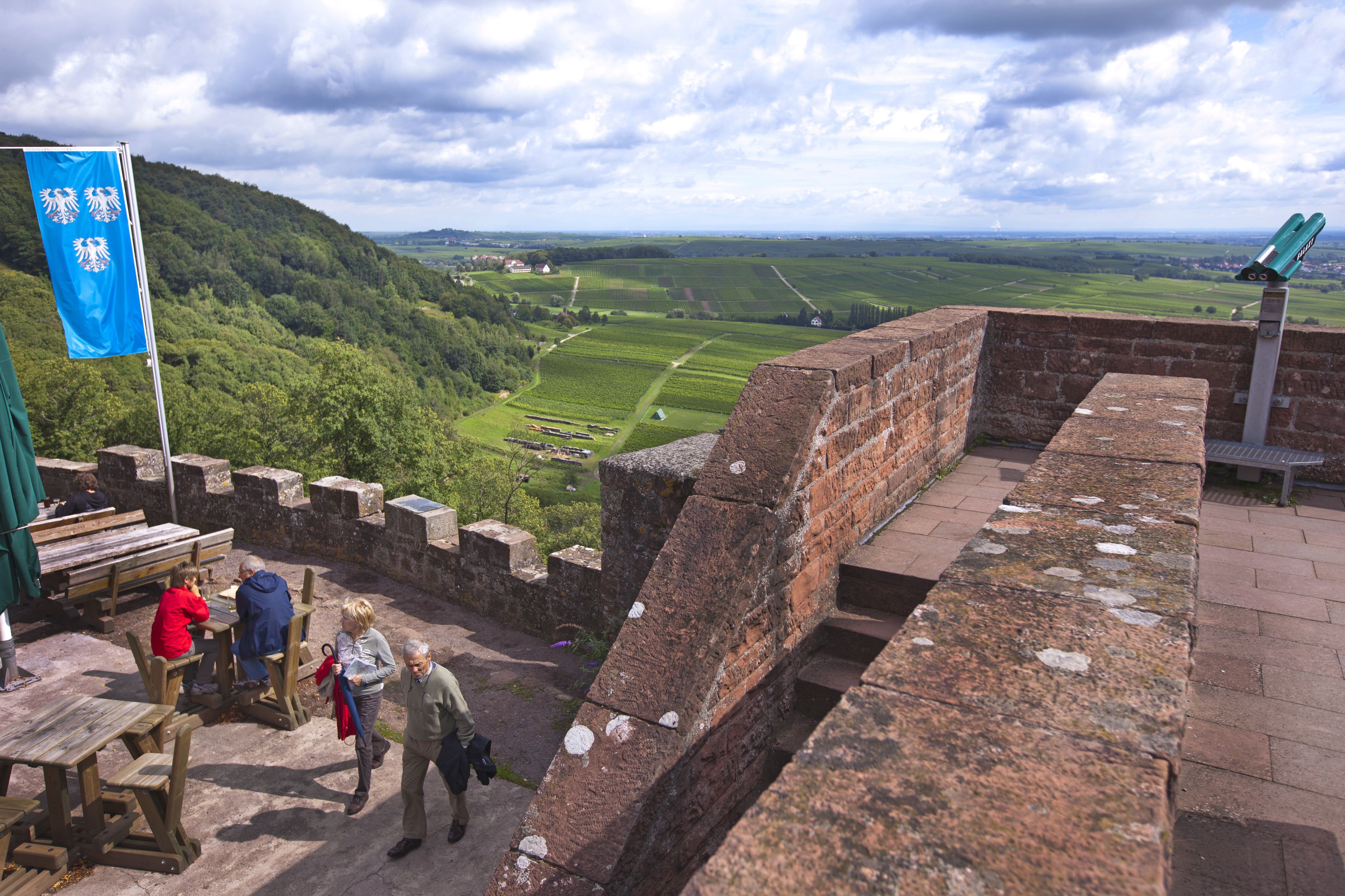 tourists at wooden tables overlooking the green valley beyond the castle walls