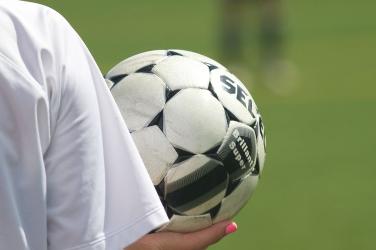 A girl holding a soccer ball in preparation for throwing it into play