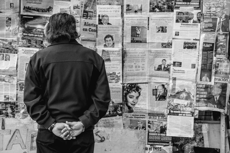 Man Standing Against Newspapers On Wall