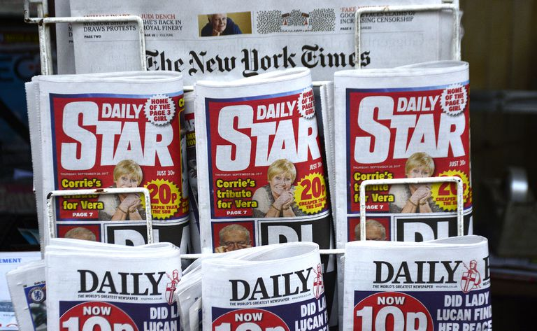 Tabloid newspapers sit at a newsstand alongside the New York Times.