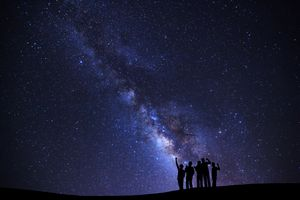 people gazing up at Milky Way in the night sky