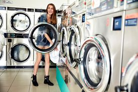 A girl loading a washing machine in a laundromat