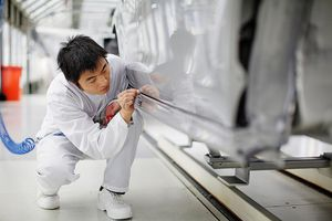 A Chinese Man Works on a Car Production Line.
