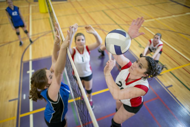 Women Spiking and Blocking a Volleyball