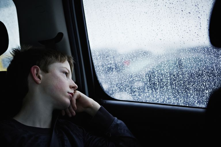 Boy gazing sadly out of window.