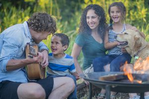 A man playing Guitar with his Family
