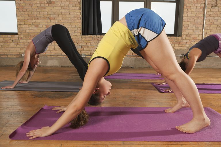 women in yoga class doing downward dog
