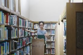 Young female Liberian arranging books in a library