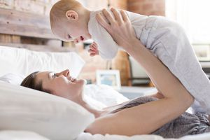 Smiling mother holding baby daughter overhead on bed
