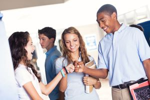 Private school friends give fist bumps before class