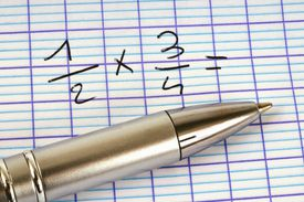 A pen on a piece of graph paper with fractions written out