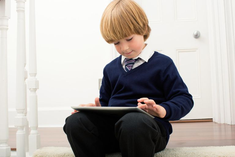 A child using an iPad on stairs.