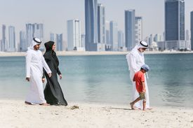 People walking on a beach in Kuwait with the city skyline behind them.