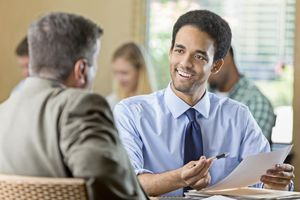 Smiling young adult male conducting a job interview
