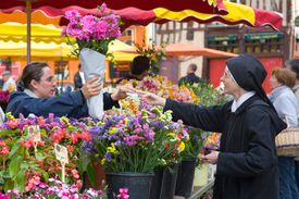 A nun buys flowers at a flower market in France