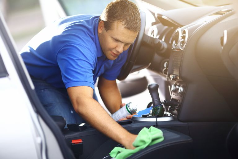 Man cleaning upholstery of his vehicle.