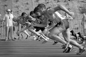 Black and white photo of runners taking off from the starting line.