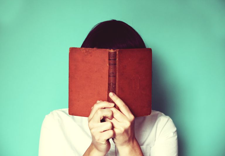 Woman holding a book in front of her face
