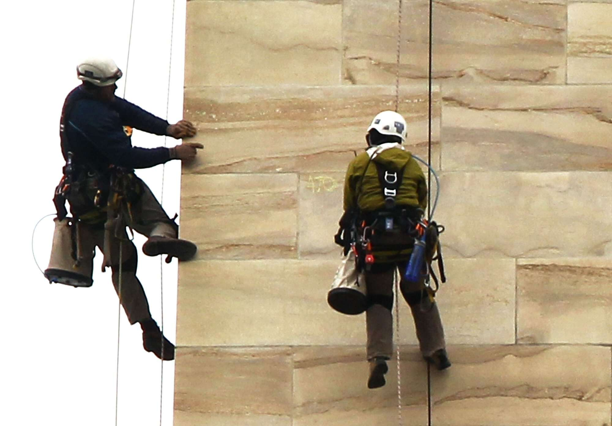 Inspectors hanging from ropes inspecting the exterior stone of the Washington Monument