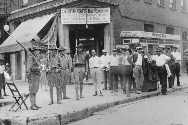 A group of African American men who have gathered in front of the Ogden Cafe, Chicago 1919