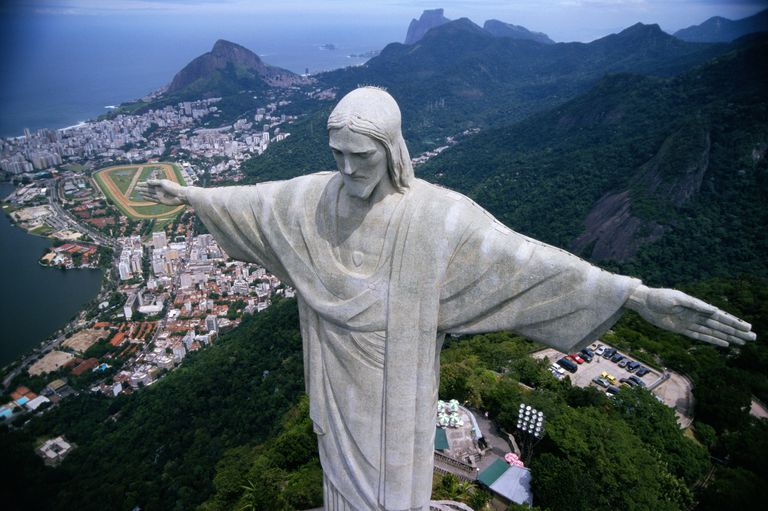 close-up of Jesus Christ statue looking down the mountains to the harbor dwellings