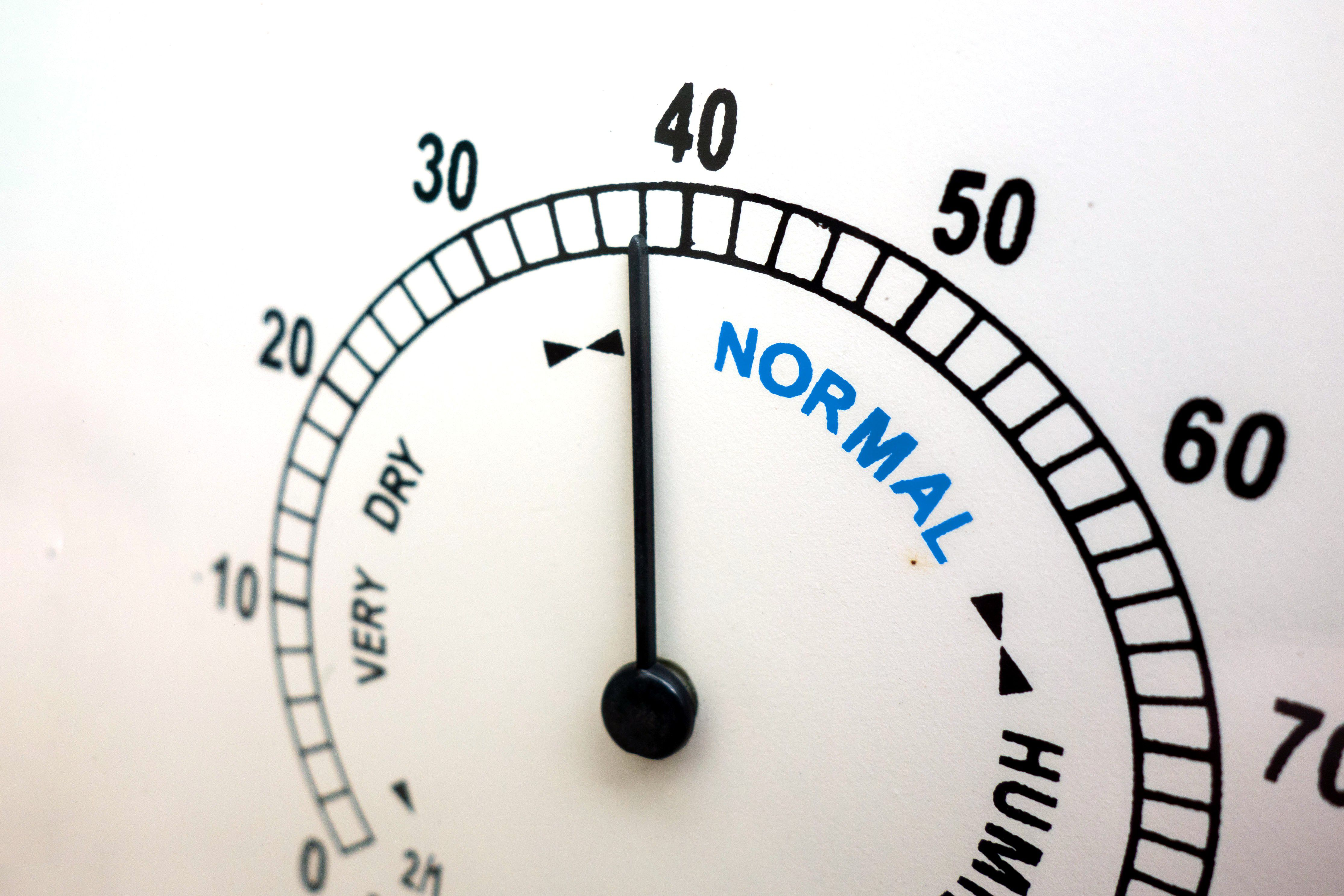 The dial on a hygrometer indicates slightly dry conditions